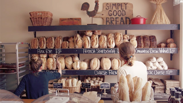 Staff at bakery with wall of breads