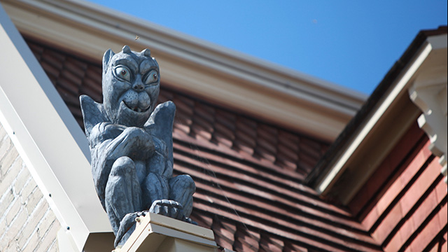 Gargoyle on red shingled roof in Warkworth
