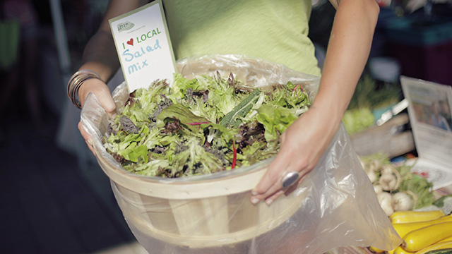 Vendor holding basket of lettuce