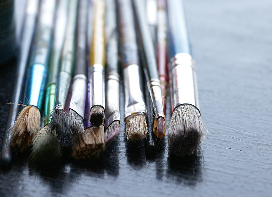 Group of paint brushes lined up on table