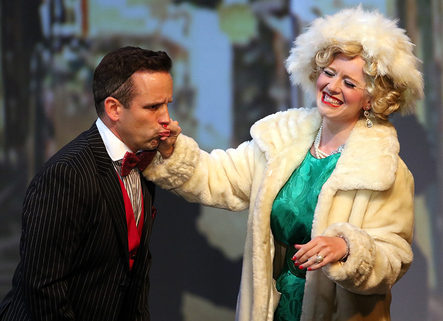 Stage performance with actress in fur jacket and feather hat holding lips of male actor in pinstripe suit