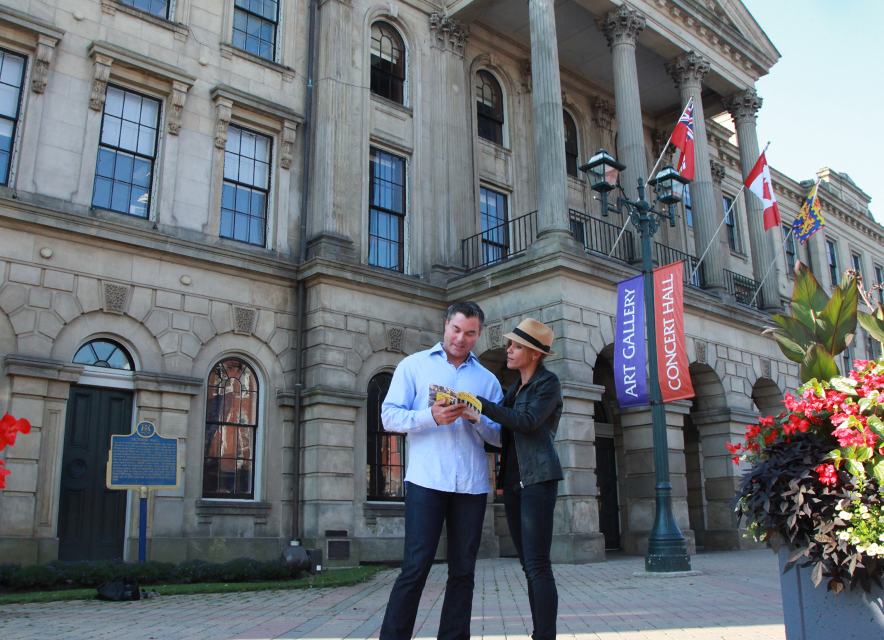 Couple looking at brochure in front of historic Victoria Hall in Cobourg