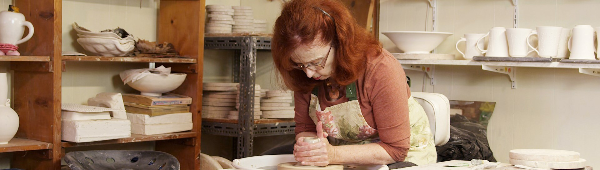 Woman working on pottery piece in her studio