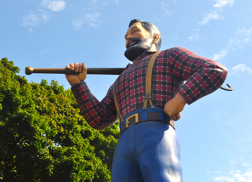 Statue of lumberjack in park on sunny day with blue sky as part of movie set