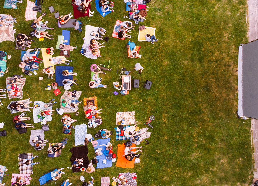 Drone shot of people sitting on blankets outside to watch movie