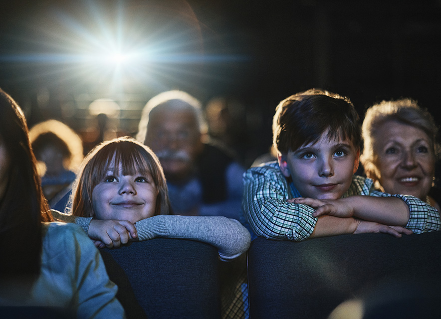 boy and girl watching a movie in theatre leaning over seats