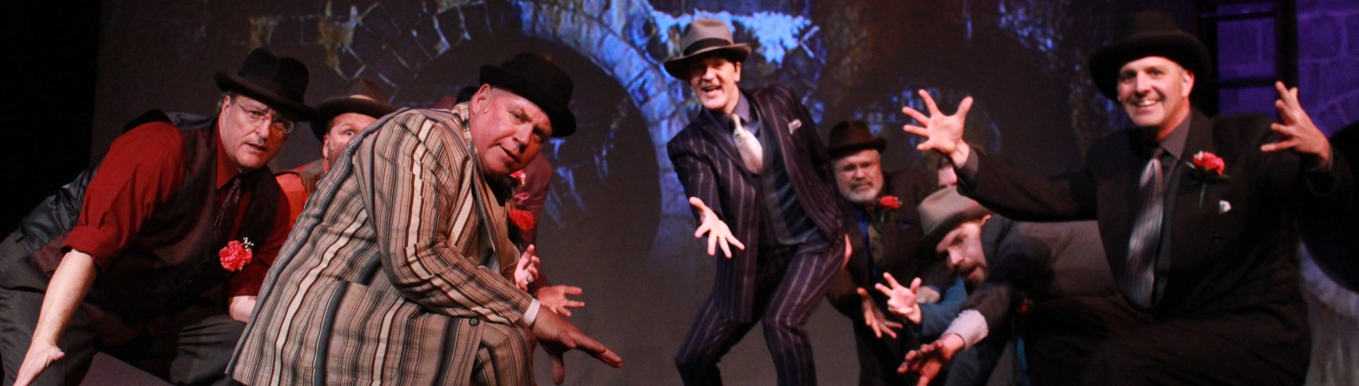 Group of male theatre actors in full costume on stage for performance of Guys and Dolls