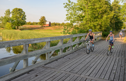 3 cyclists riding over wooden bridge in farmland setting