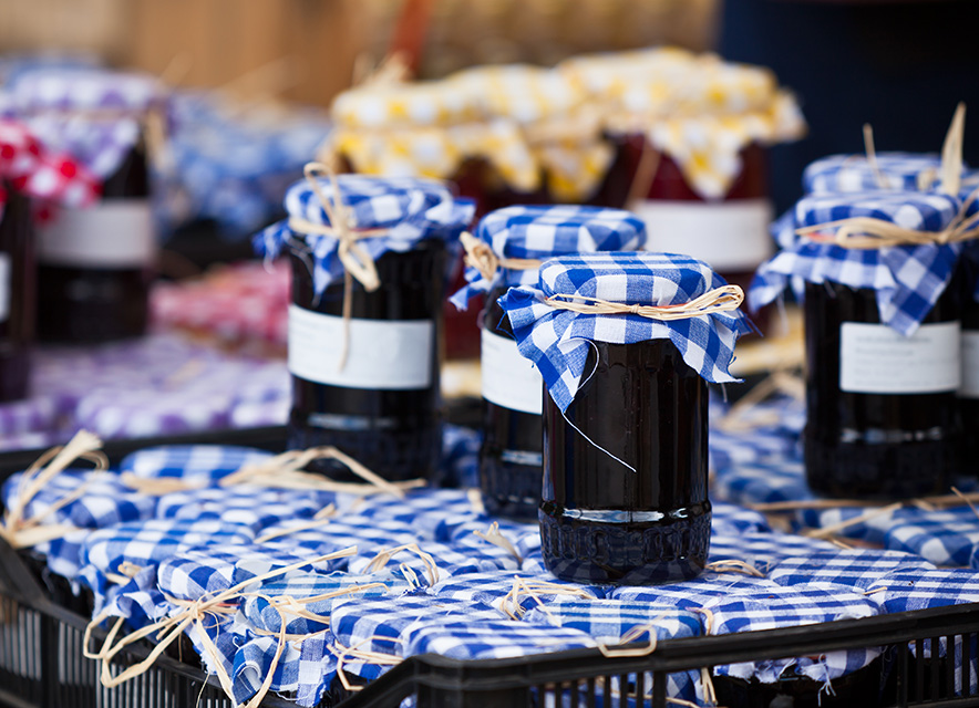 Jars of preserves at market with gingham fabric lid covers