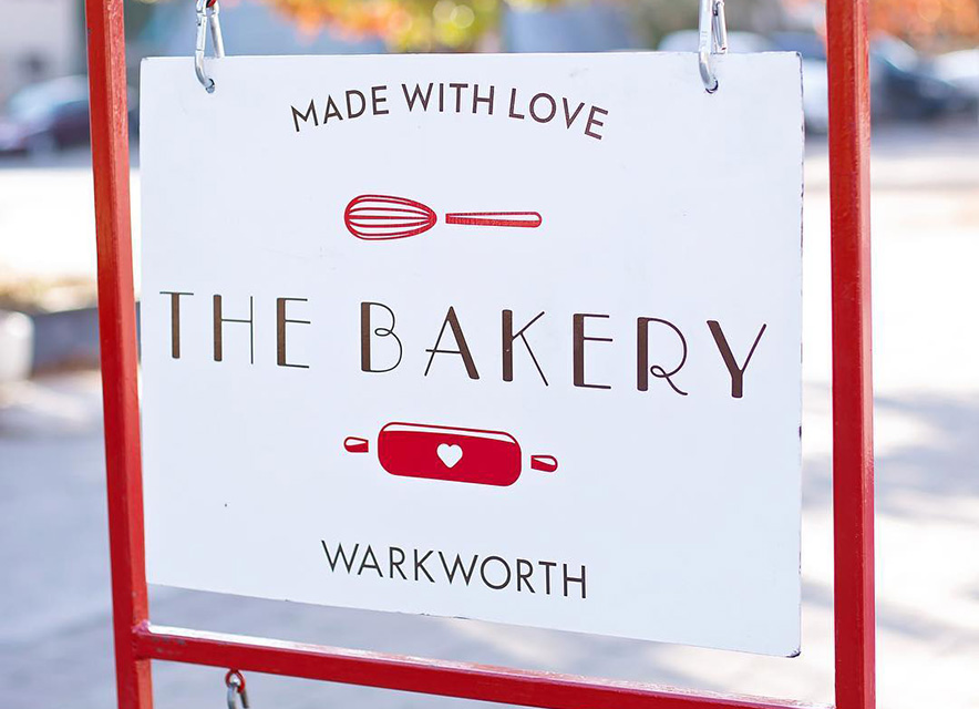 Outdoor sign placard for The Bakery Warkworth with red sign holder and blurred trees in background