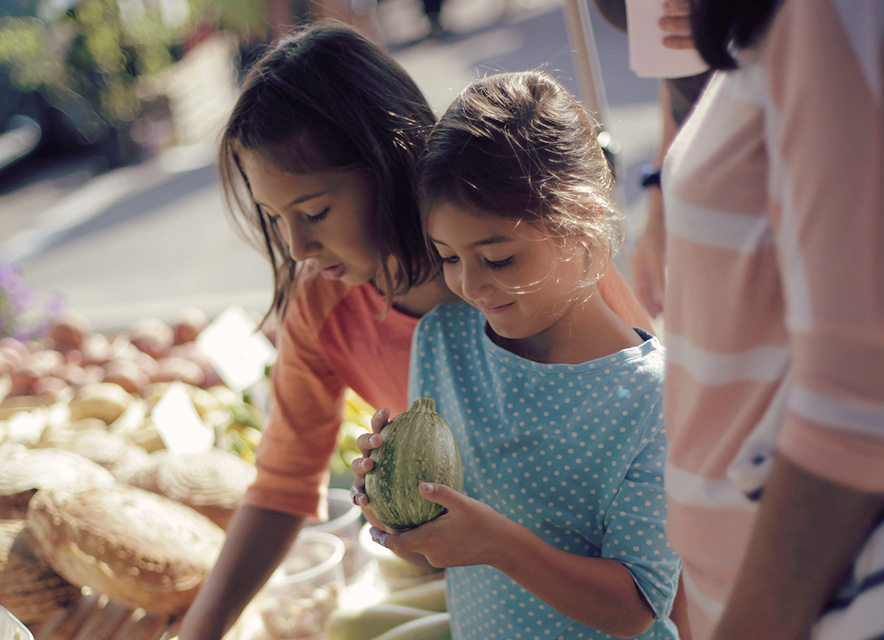 Two young girls holding fresh vegetables at a market with mother looking over them