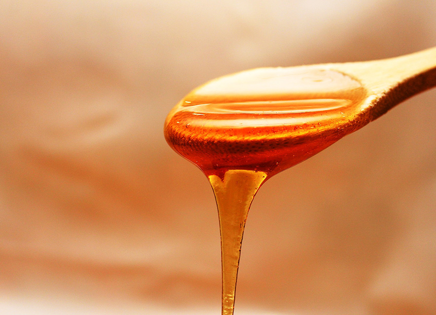 Honey dripping from wooden spoon on neutral background