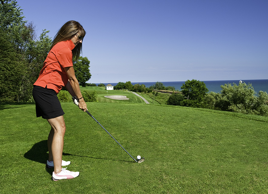 Woman wearing red shirt and black golf skirt about to take a swing at a golf ball on course with lake in background