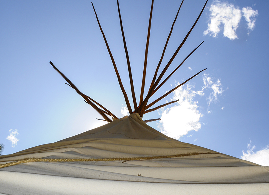 Top of teepee with blue sky in background