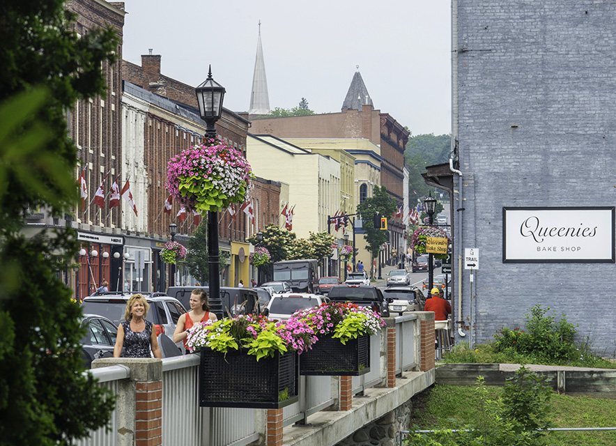 Woman walking on sidewalk across bridge downtown Port Hope Walton Street