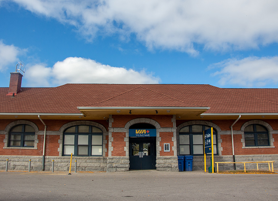Exterior of VIA Rail Station Cobourg with blue sky and white clouds