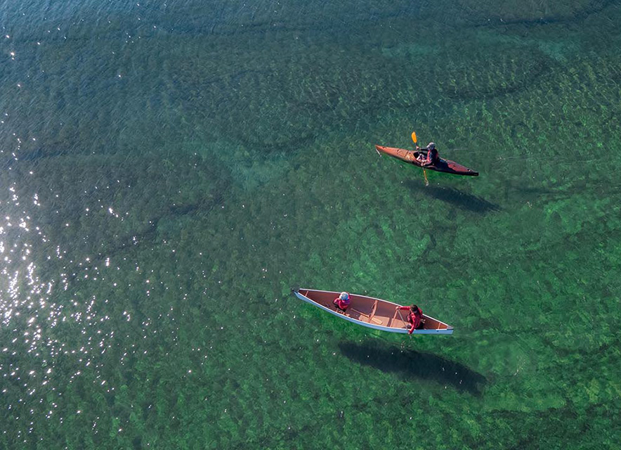 Drone shot of person in kayak and parent and child in canoe over clear green water