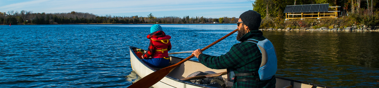 Father and daughter paddling away from camera in canoe