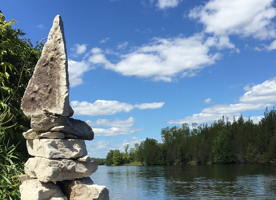 Inukshuk rock sculpture at edge of Trent River
