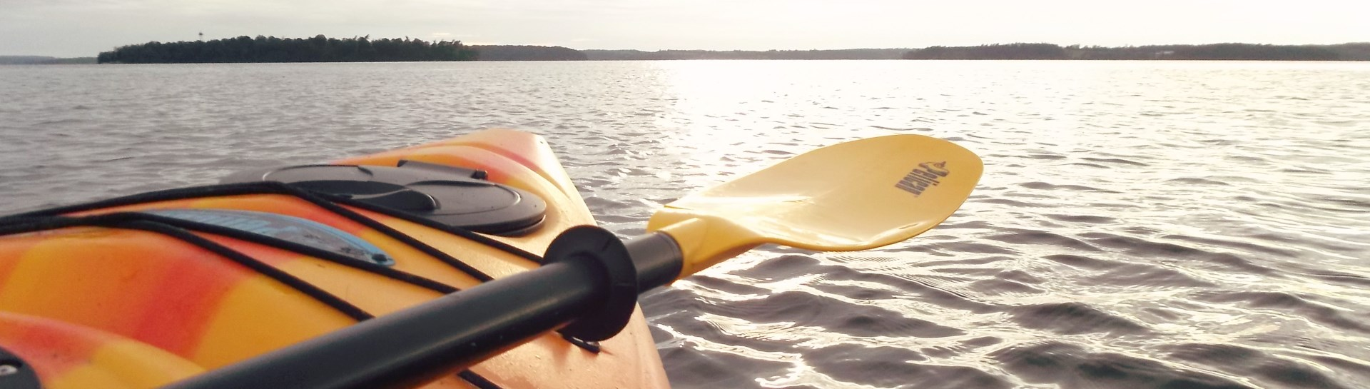 Tip of kayak and oar on lake with land in background