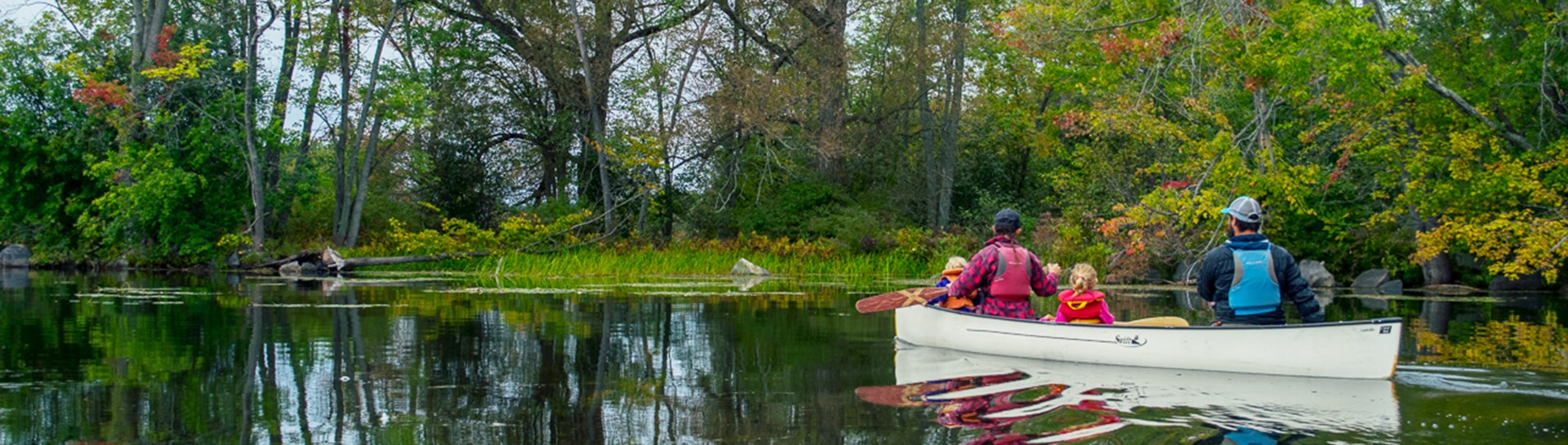 Family canoeing through Percy Reach Trent Severn Waterway in fall