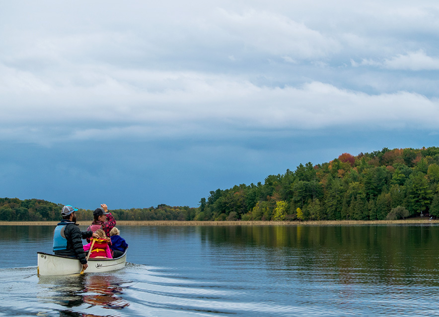 Family canoeing across flat lake with fall colours in background
