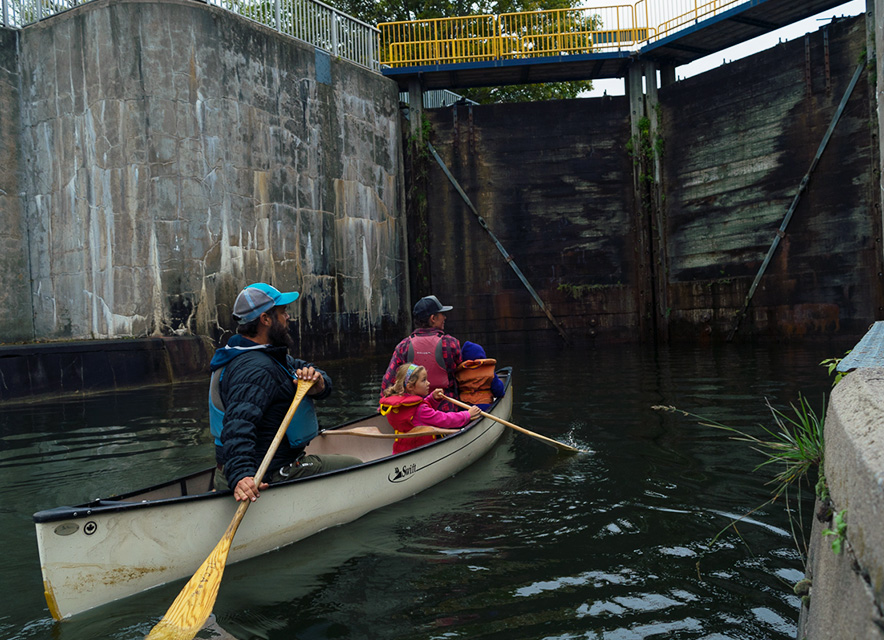 Family paddling canoe to enter lock system