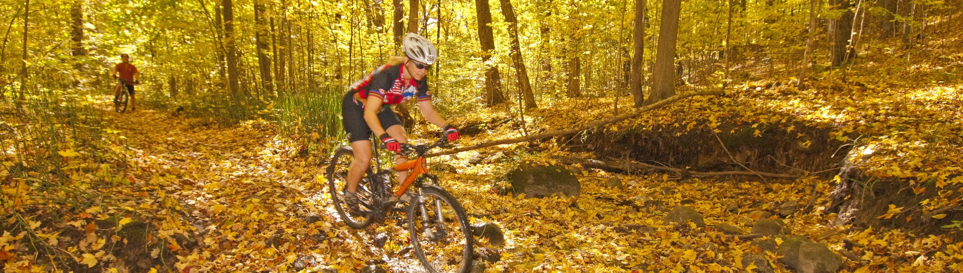 Woman in racing clothes mountain biking through Ganaraska Forest in fall
