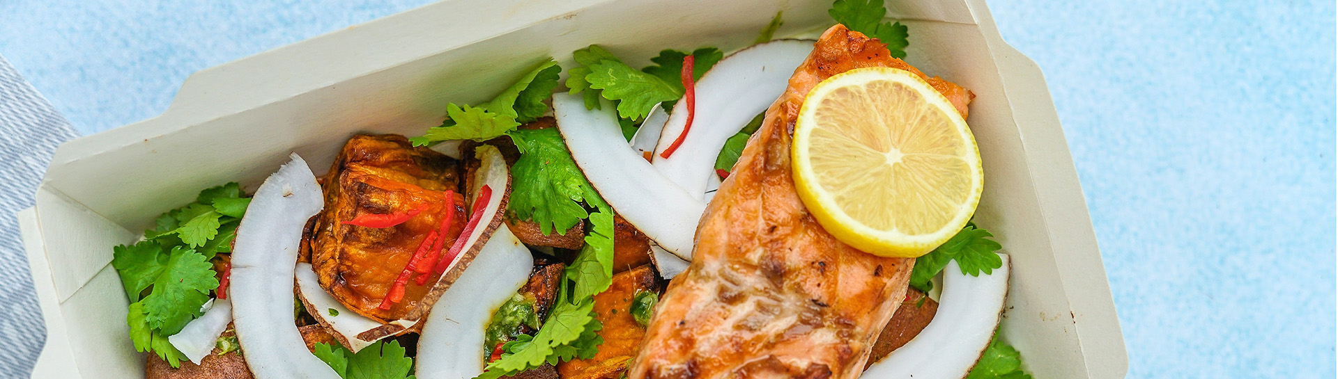 Takeout tray of salad with salmon