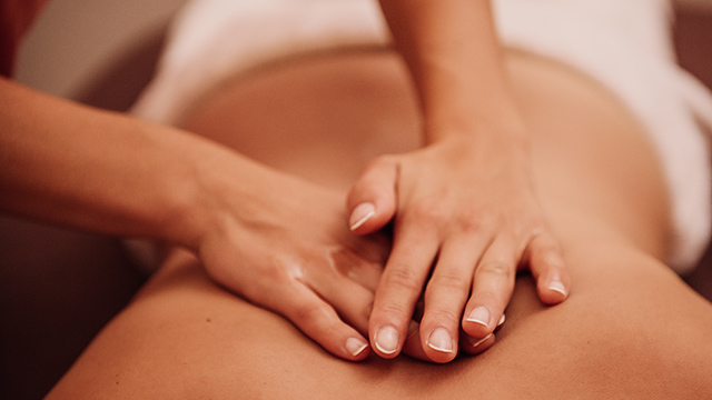 Close up of hands on woman's back for massage