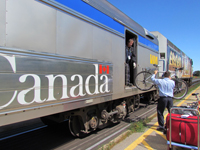 bicycle being handed to train attendant at VIA Rail baggage car