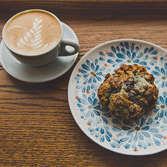 Blueberry scone on hand painted plate with latte on the side with art in foam