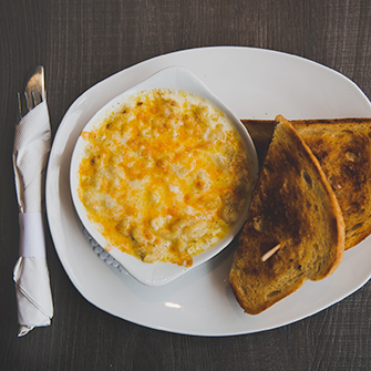 Oven baked macaroni and cheese with sandwich on white plate with fork and knife in napkin beside plate