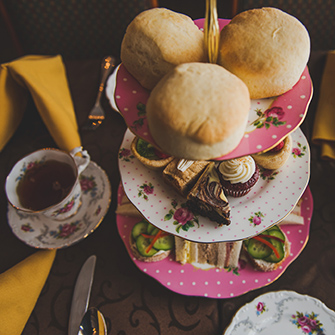Tea tray with finger sandwiches, desserts and biscuits with tea in cup beside