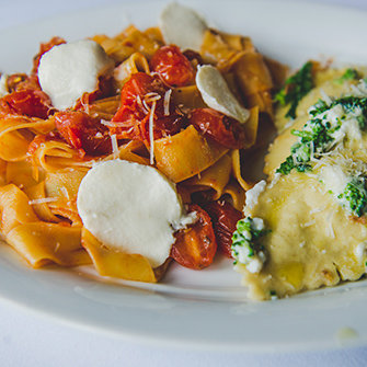 Pasta noodles and ravioli on white plate