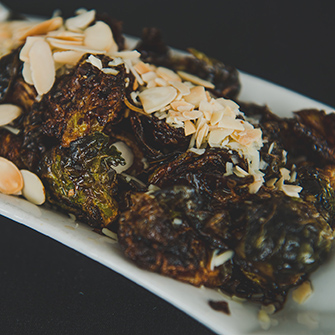 Fried brussel sprouts with slivered almonds on white plate with black background