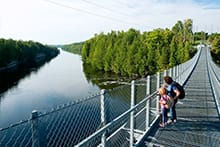 Mother and daughter walking on suspension bridge over water