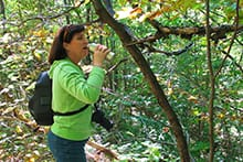 Woman drinking for water bottle on hike