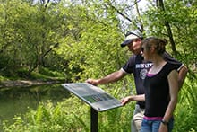 Two people looking at information plaque on trail