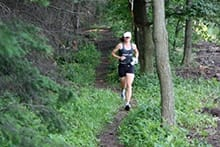 Woman running on wooded trail