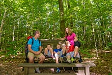Family sitting on park bench in nature reserve