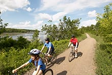 Three people riding bikes along waterfront trail
